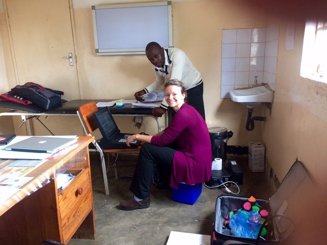 Michelle Kvalsund, (sitting at a computer D.O. Assistant Professor within MSU's Department of Neurology and Ophthalmology, at Bauleni Health Centre in Lusaka, Zambia and HIV Counselor & Research Assistant, Martin Simunyama, (standing behind Michelle) with an electromyography (EMG) and nerve conduction study machine donated by Michigan State University and Sparrow Health Systems